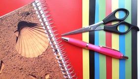 Coloree el fondo plano de la composición de la geometría de los papeles con la pluma y las tijeras Foto de archivo