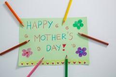 Coloree el lápiz arreglado alrededor de tarjeta de felicitaciones del día de madres Fotografía de archivo