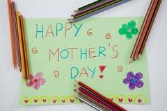 Coloree el lápiz arreglado alrededor de tarjeta de felicitaciones del día de madres Foto de archivo libre de regalías