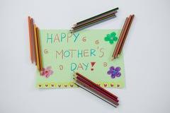 Coloree el lápiz arreglado alrededor de tarjeta de felicitaciones del día de madres Foto de archivo