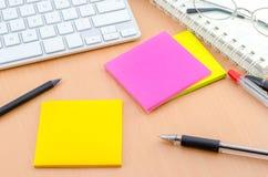 Coloree el papel de nota con la pluma en el escritorio del ordenador Foto de archivo