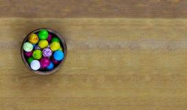 Coloree la base del cuenco de madera del día de fiesta con la opinión de los gumballs del arco iris desde arriba sobre un tablero Fotos de archivo libres de regalías