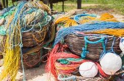 Coloree la red de pesca, flotadores, cuerda de nylon en la cesta en el banco foto de archivo