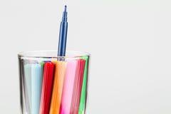 Coloree las plumas en vidrio con una pluma más altas de las otras Imágenes de archivo libres de regalías