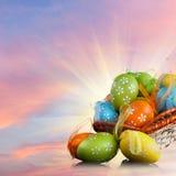 Coloree los huevos de Pascua en cesta contra el cielo y las nubes Imágenes de archivo libres de regalías