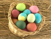 Coloree los huevos de Pascua en cesta marrón en el primer de la paja Fotografía de archivo