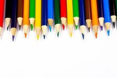 Coloree los lápices alineados en fila contra un fondo blanco fotos de archivo