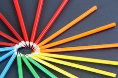 Coloree los lápices arreglados en un izquierdo superior del círculo en el fondo oscuro, visión superior Foto de archivo
