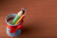 coloree los lápices en lata con los lápices verdes grandes en la tabla de madera en fondo negro Fotografía de archivo