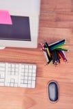 Coloree los lápices en tarro por el ordenador en el escritorio Foto de archivo