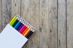 Coloree los lápices en una caja en el tablón de madera Fotos de archivo