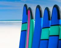 Coloree los tableros de resaca en una pila por el océano Imagen de archivo