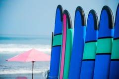 Coloree los tableros de resaca en una pila por el océano Imágenes de archivo libres de regalías