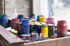 Coloree los tarros y la témpera en la tabla de funcionamiento en laboratorio de cerámica en pavo imágenes de archivo libres de regalías