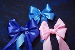 Colores azules del arco de tres regalos, rosados y azules de cintas de satén en a fotos de archivo