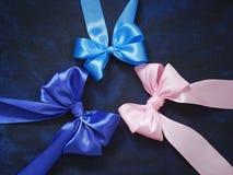 Colores azules del arco de tres regalos, rosados y azules de cintas de satén en a fotografía de archivo libre de regalías