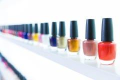 Colores coloridos del esmalte de uñas en fila en el salón de los clavos en blanco Fotos de archivo