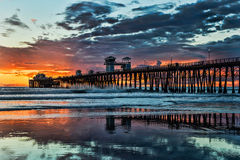 Colores de la puesta del sol en el embarcadero de la costa Imagenes de archivo