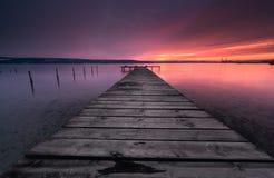 Colores de la puesta del sol y del embarcadero oxidado viejo Imagen de archivo