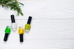 Colores de las botellas verde natural y amarillo del esmalte de uñas imagen de archivo
