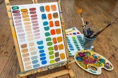 Colores de mezcla del ejercicio del color de la pintura con los cepillos y el pallete del caballete Imagen de archivo libre de regalías