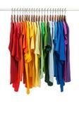 Colores del arco iris, camisas en perchas de madera Fotografía de archivo