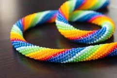 Colores del arco iris del collar en superficie de madera oscura Imagenes de archivo