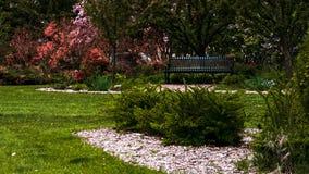 Colores del jardín con el banco en la composición imagenes de archivo