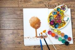 Colores y cepillos con la pintura del estudiante Foto de archivo libre de regalías
