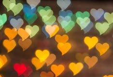 Colorez Bokeh sur un fond foncé avec des coeurs Photos libres de droits