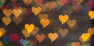 Colorez Bokeh sur un fond foncé avec des coeurs Images libres de droits