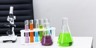 Colorez l'eau dans le tube à essai, les microscopes et le becher Copiez l'espace photo libre de droits