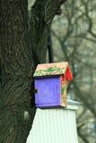 Colorez la volière sur un arbre dans la ville photographie stock