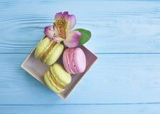 Colorez le biscuit gastronome de macaron dans une boîte sur un fond en bois bleu, fleur d'alstroemeria de confiserie Photos libres de droits