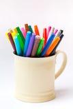 Colorez le stylo dans la tasse sur le fond blanc, concept de l'espace de fonctionnement d'artiste Photo stock