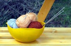 Colorez les écheveaux du fil de laine, des aiguilles de tricotage et du crochet de crochet dans une grande cuvette jaune Images stock