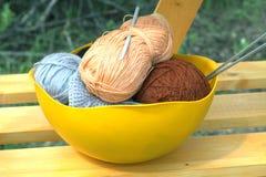 Colorez les écheveaux du fil de laine, des aiguilles de tricotage et du crochet de crochet dans une grande cuvette jaune Photographie stock libre de droits