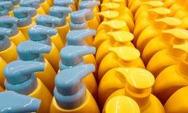 Colorez les bouteilles en plastique avec des couvercles dans une rangée Image stock