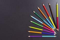 Colorez les crayons éventent sur le fond noir avec l'espace libre Concept d'art Images stock