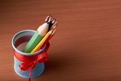 colorez les crayons dans la boîte en fer blanc avec de grands crayons verts sur la table en bois sur le fond noir Photographie stock