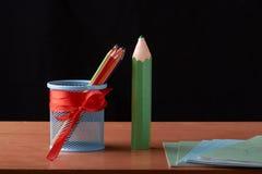 colorez les crayons dans la boîte en fer blanc avec de grands crayons verts sur la table en bois sur le fond noir Image stock