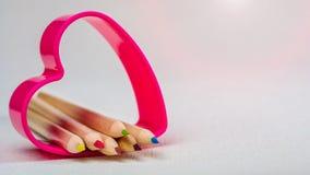 Colorez les crayons s'étendant dans le symbole rouge de coeur et représentez l'amour au dessin de créativité Photographie stock libre de droits