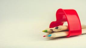 Colorez les crayons s'étendant dans le symbole rouge de coeur et représentez l'amour au dessin de créativité Image libre de droits