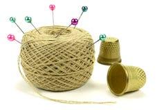 Colorez les goupilles pour coudre avec la bobine des fils et un dé sur un fond blanc Photo libre de droits