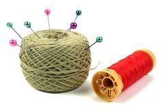 Colorez les goupilles pour coudre avec la bobine des fils sur un fond blanc Photo libre de droits
