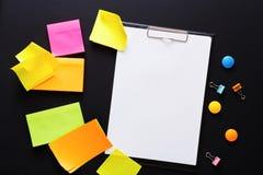 Colorez les notes et le papier de note sur le conseil noir, copient l'espace Photos stock