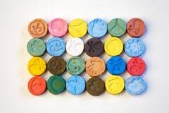 Colorez les pilules extasy de diverses conceptions employées par le marchand de MDMA Image libre de droits
