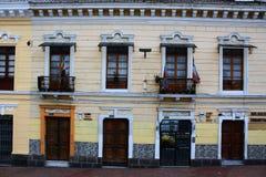 Colorfol rad av fönster och dörrar med flaggor på en brant kulle i quito Ecuador royaltyfria bilder
