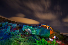 Colorful Abandoned Junked Car. Abandoned Car lit with multiple gelled flash bursts at night Stock Photos