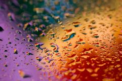 Colorful abstract background of purple, blue, red and orange beads of water. royalty free stock photos